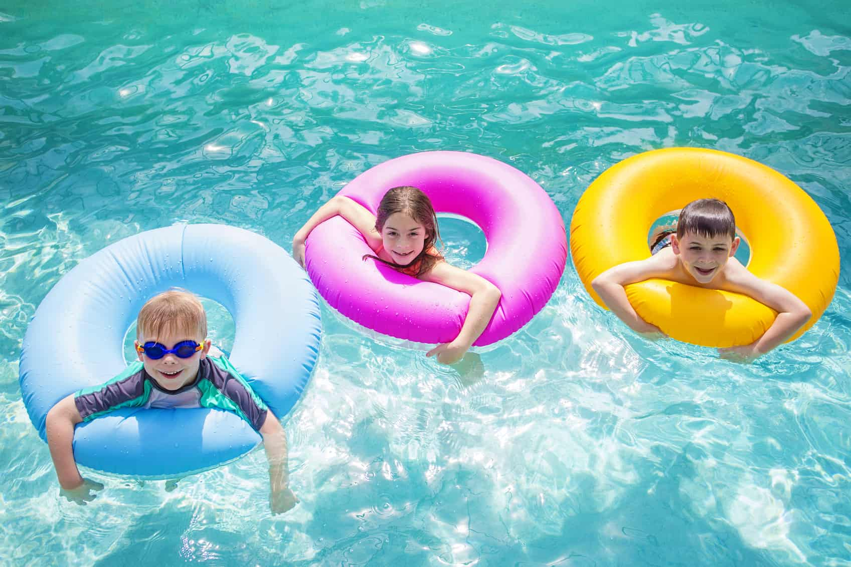 Group Of Kids Playing On Inflatable Tubes In Swimming Pool