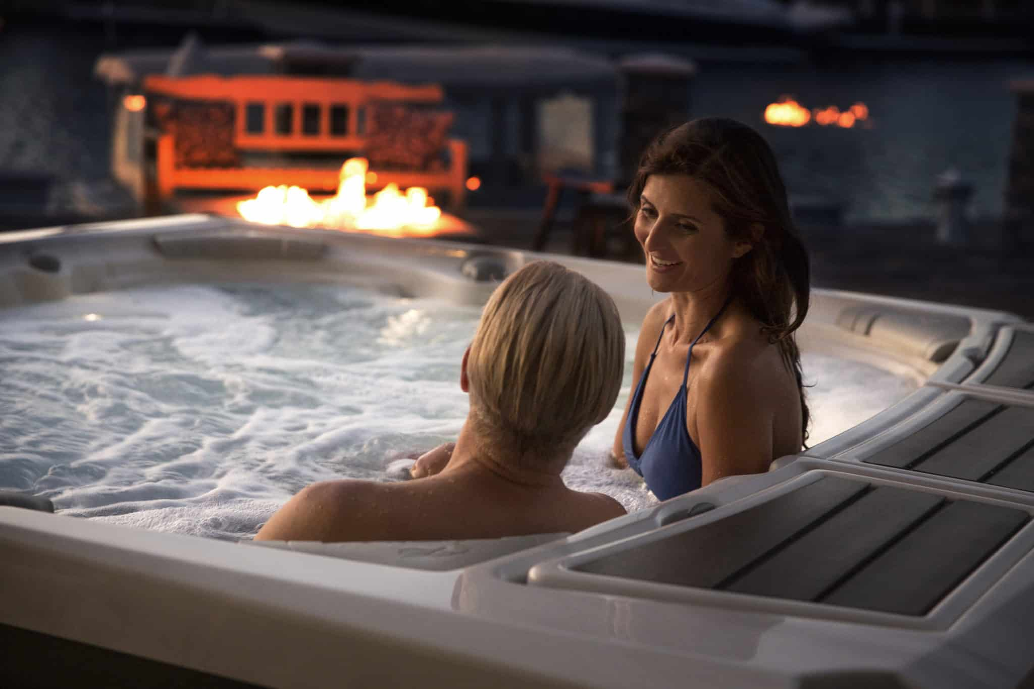 Man and woman relaxing in a hot tub by the fire.