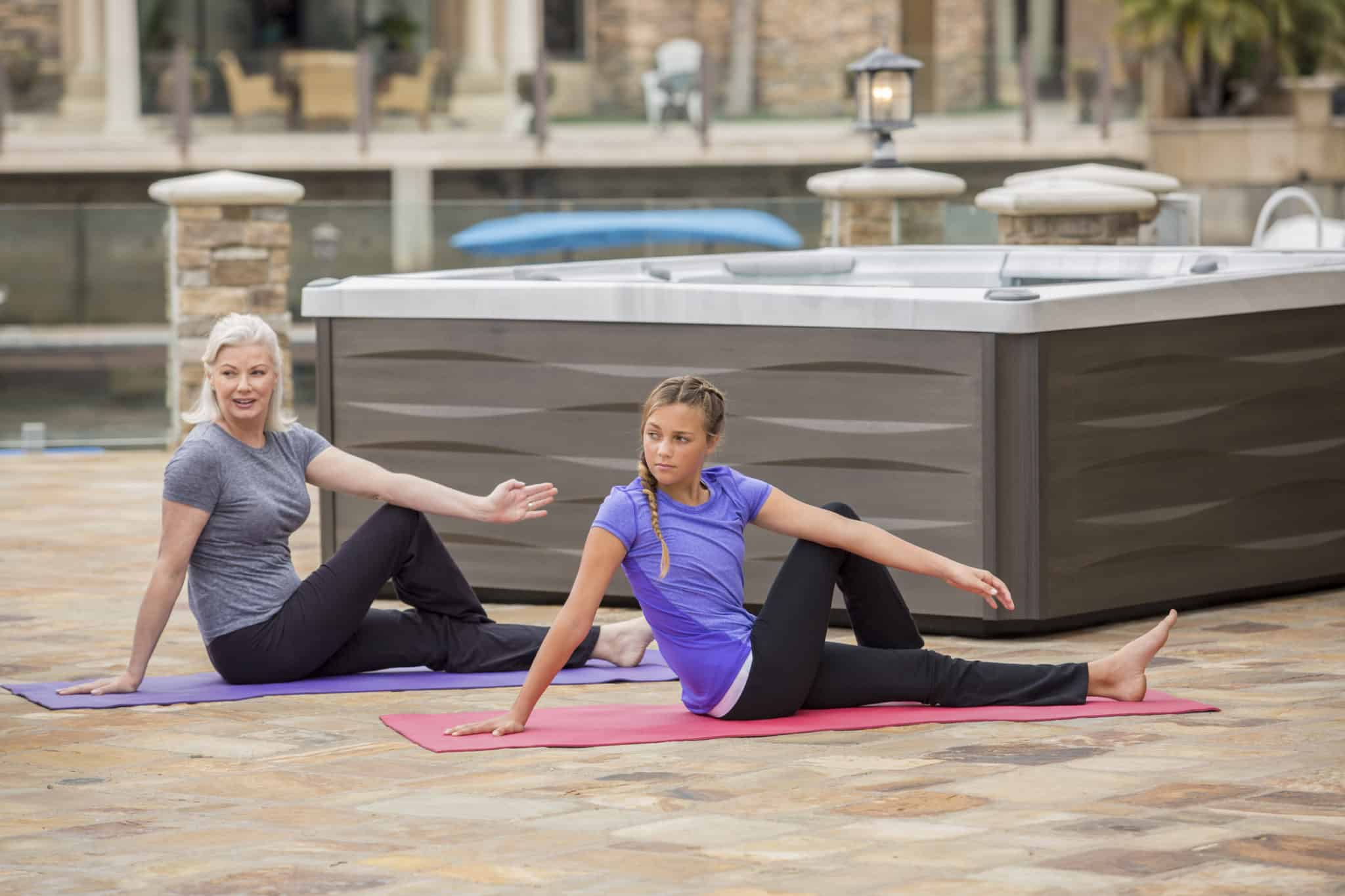 Grandmother and granddaughter doing yoga beside a hot tub.