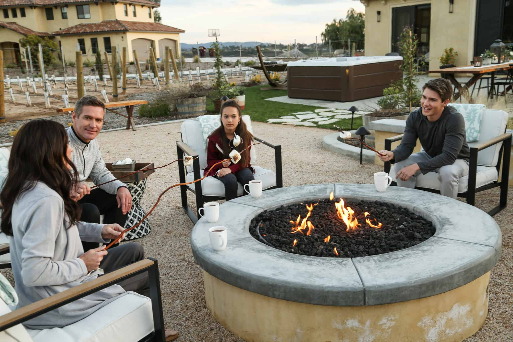 Family sitting by the fire with a hot tub and hammock in the background