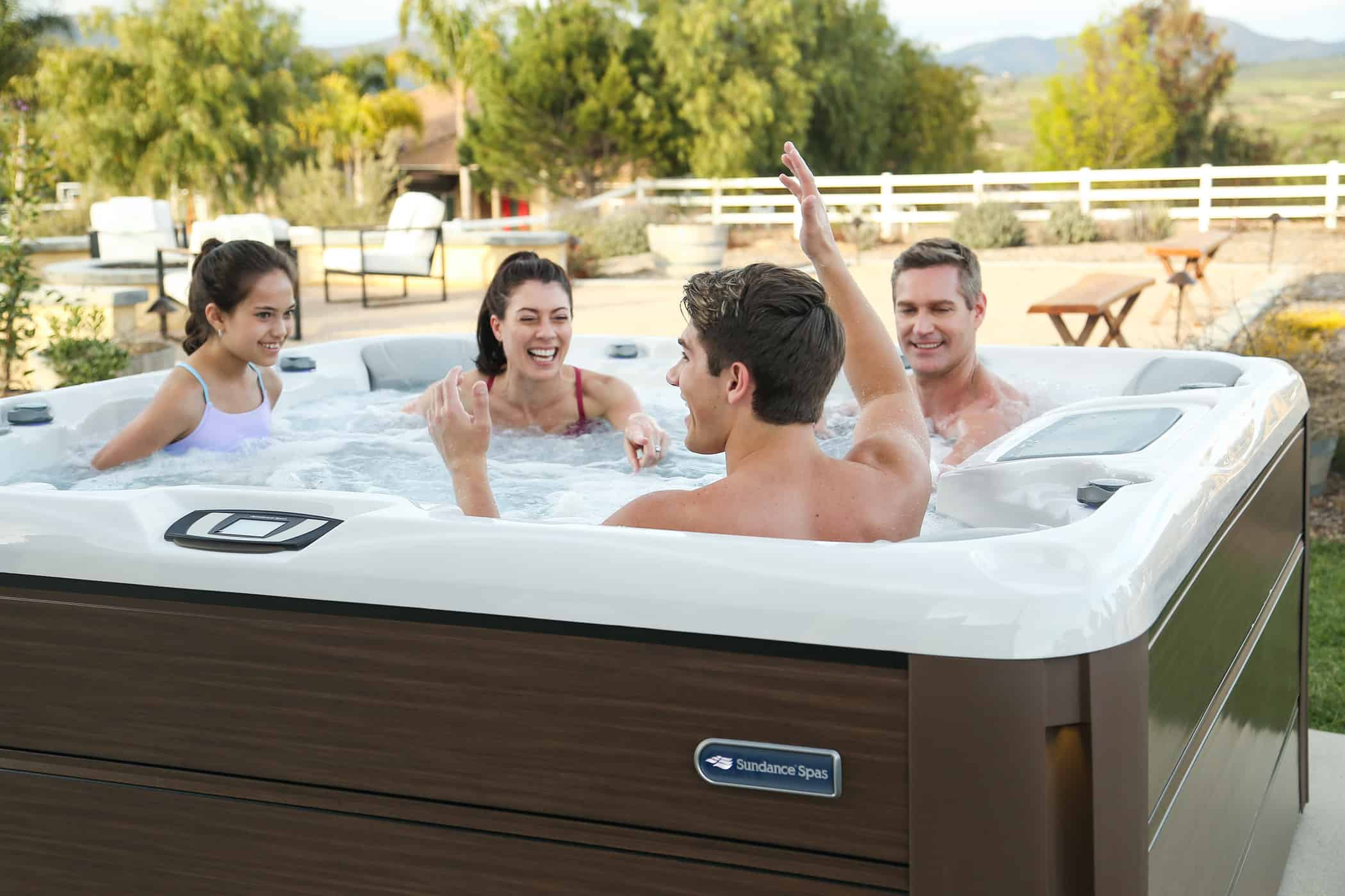 Optima Sundance Spas hot tub installation with happy family inside.