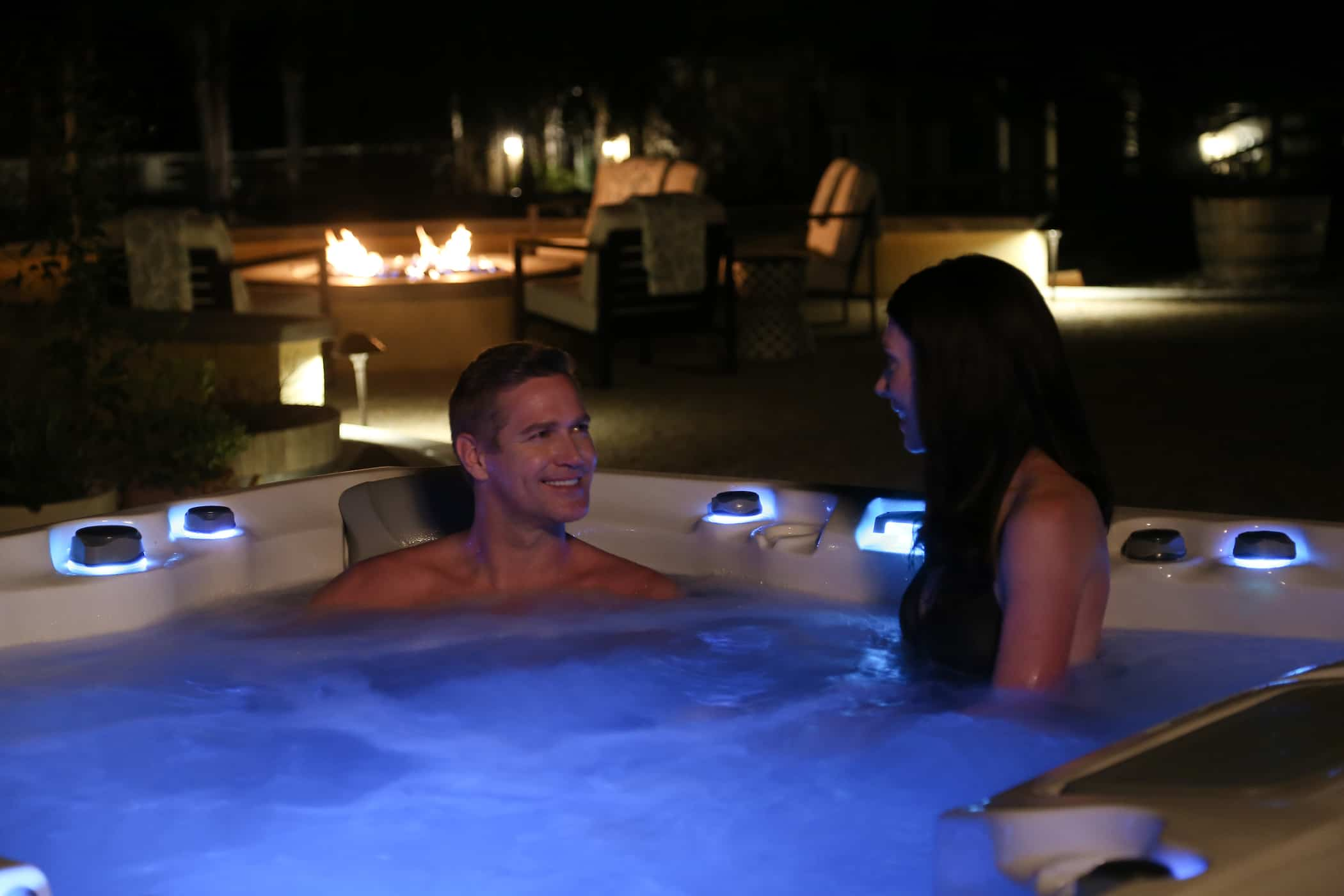 Man and woman soaking in a hot tub at night.
