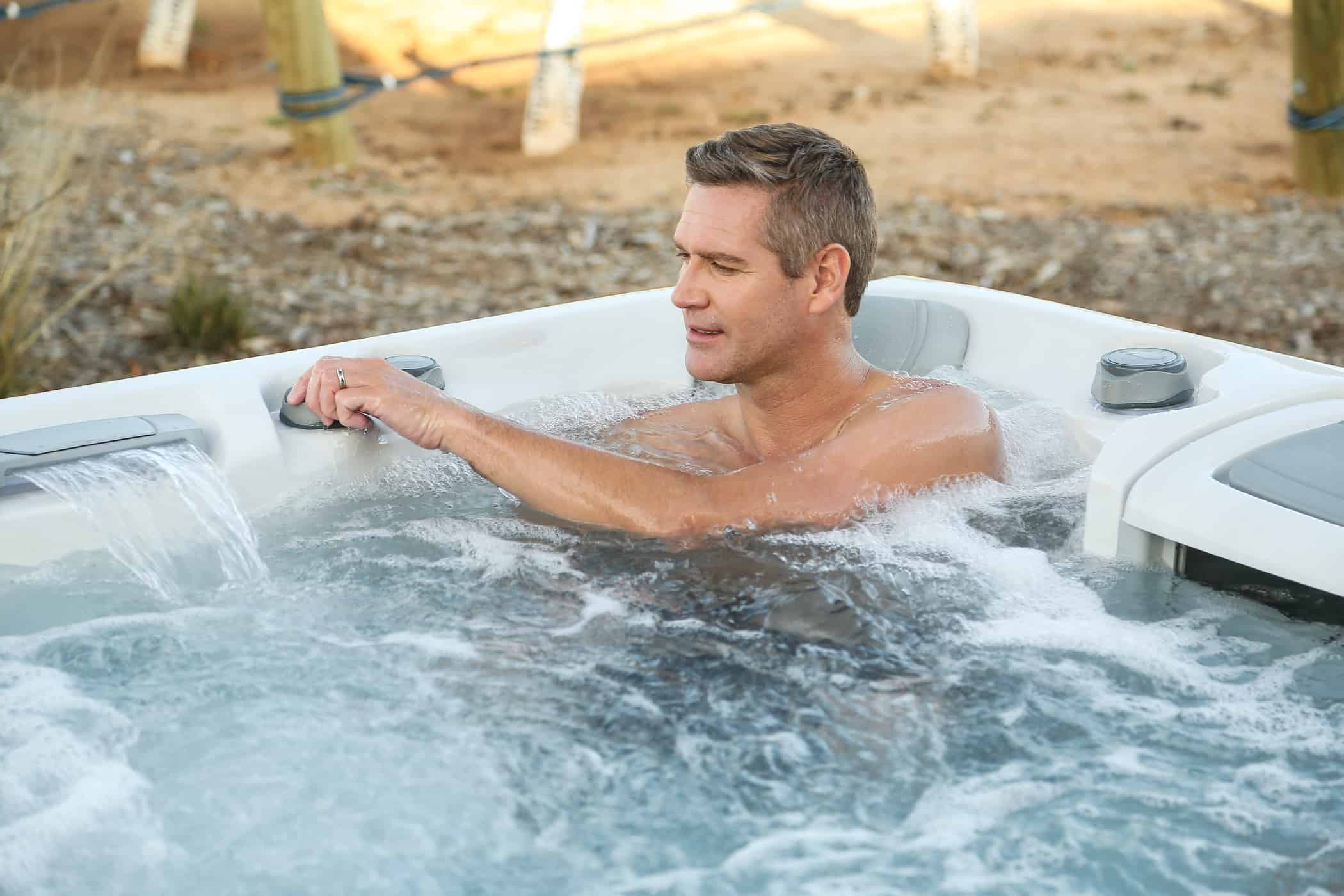 Man soaking in a Sundance Spas hot tub.